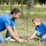 homeschooling father and son planting tree
